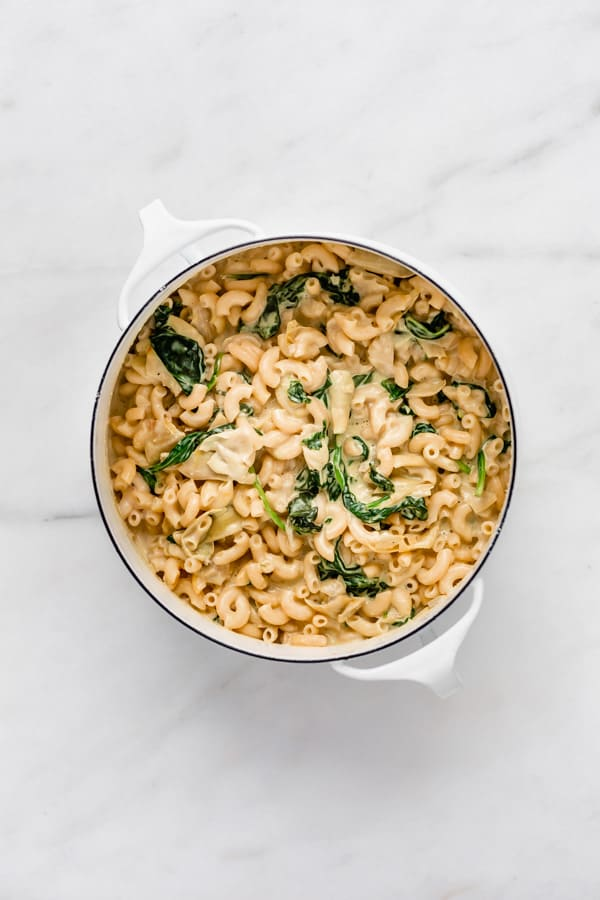vegan spinach and artichoke mac and cheese in a white pot