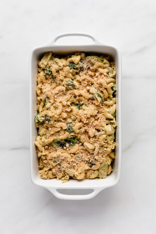 vegan spinach and artichoke mac and cheese in a white baking dish topped with breadcrumbs