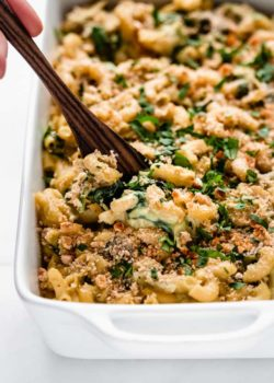 A serving spoon scooping up a spoonful of spinach and artichoke mac and cheese