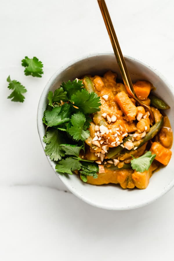 A bowl of vegetable korma with cilantro and crushed cashews on top