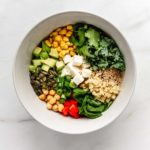 a bowl of quinoa salad with vegetables, feta cheese and seeds in it