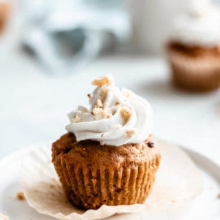 a carrot cupcake topped with coconut whipped cream and crushed walnuts