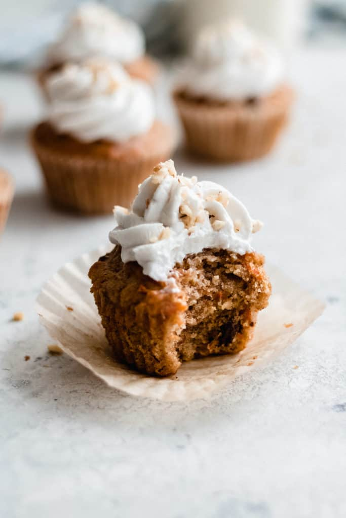 a carrot cake cupcake with a bite taken out of it