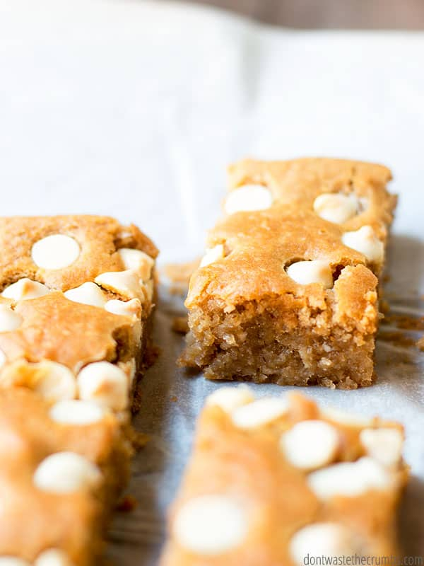 blondies made with a can of white beans, covered with white chocolate chips on a piece of white parchment paper