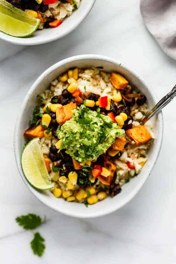 burrito bowl in a white bowl with corn, black beans, peppers, and a sliced lime topped with guacamole and chopped cilantro