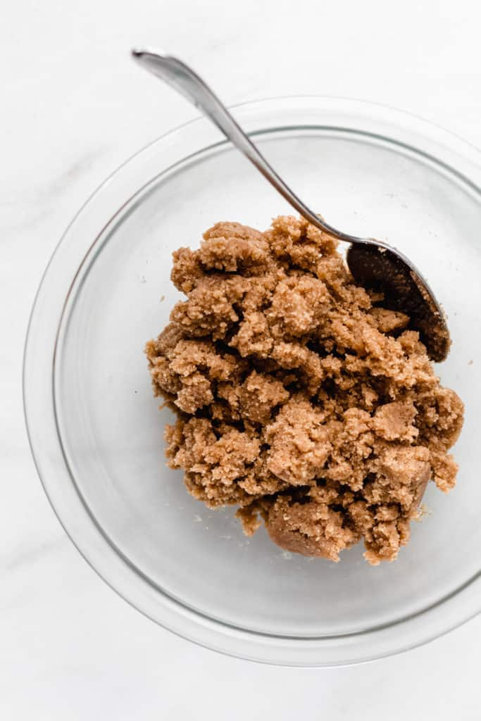 almond flour cookie dough in a clear mixing bowl with a spoon