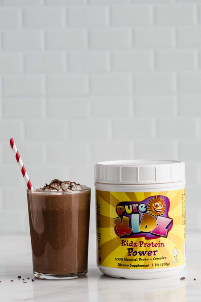 a glass of frozen hot chocolate next to a container of protein powder