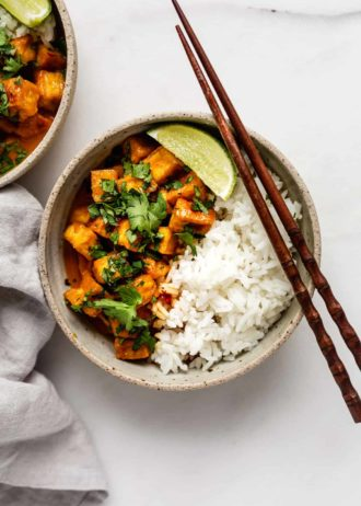 a bowl of coconut curry tofu with chopsticks on top and a napkin on the side