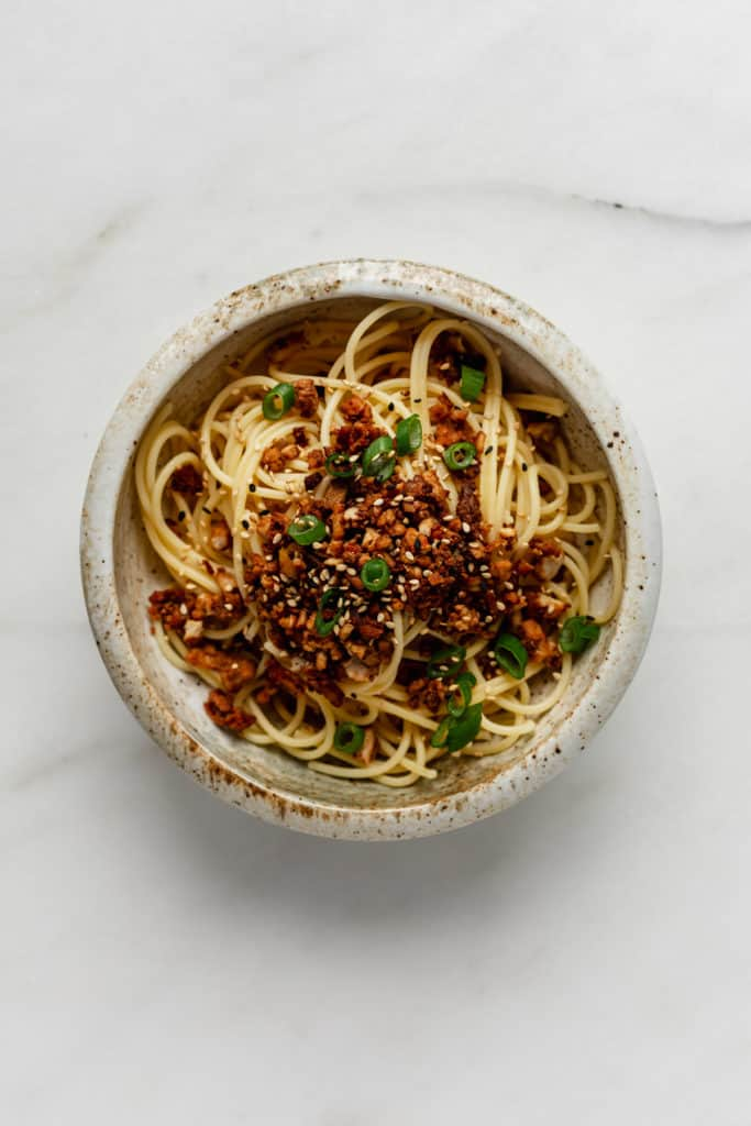 A bowl of noodles topped with vegan ground meat and green onions