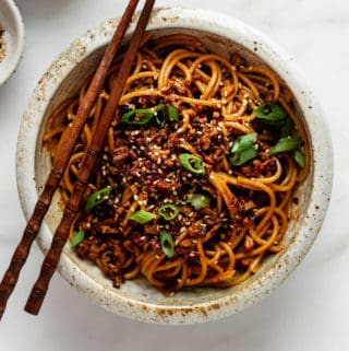 Vegan dan dan noodles topped with green onions and sesame seeds
