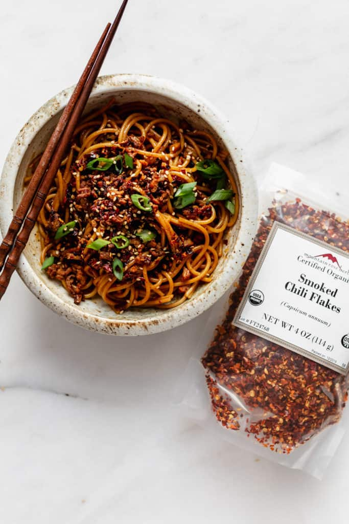 a bowl of dan dan noodles with smoked chili flakes on the side