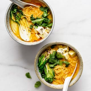 two bowls of vegetarian laksa on a marble board