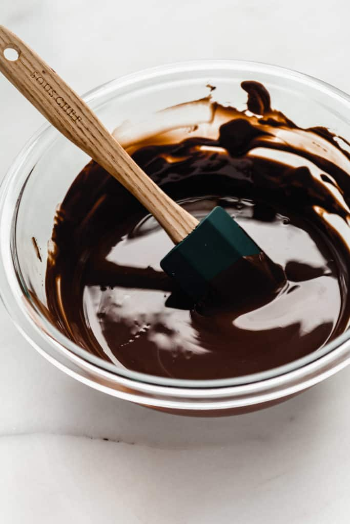 a mixing bowl of melted chocolate with a spatula in it