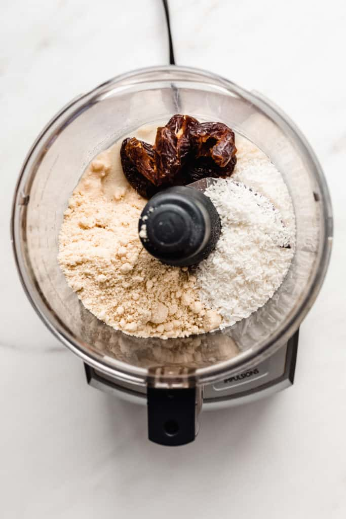 a food processor with shredded coconut, almond flour and dates
