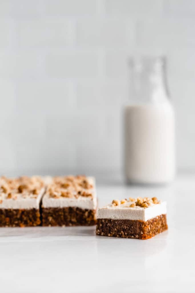 raw carrot cake bars on a marble counter with a bottle of milk in the background