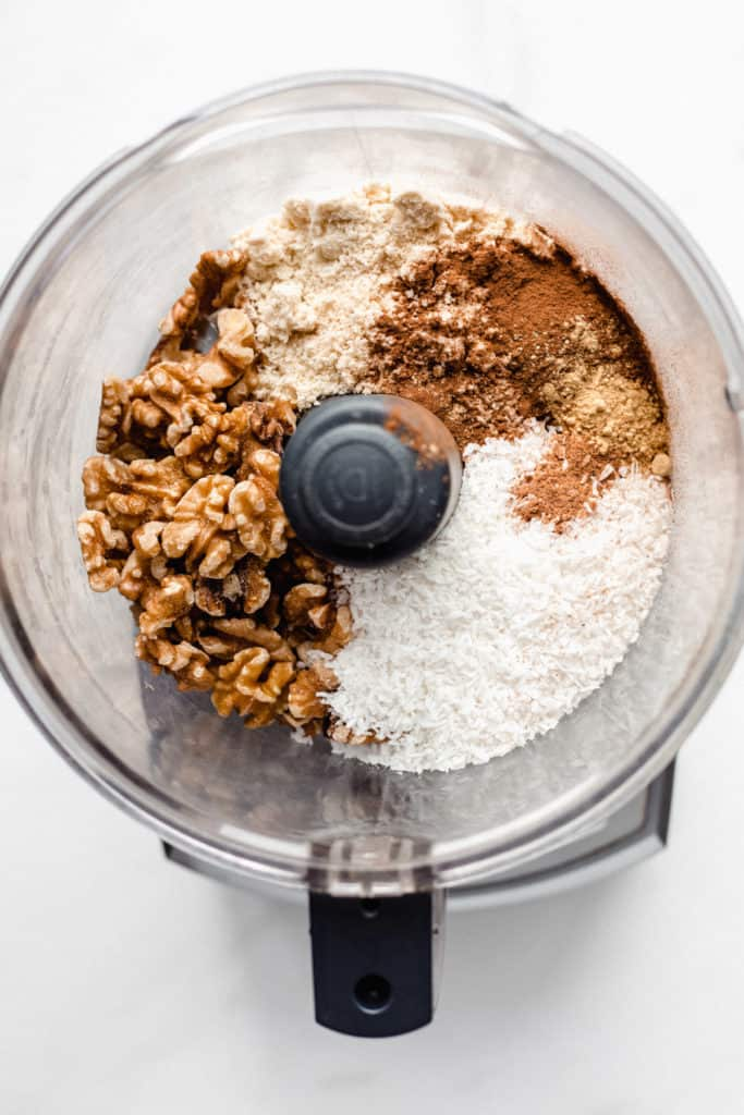 a food processor with shredded coconut and nuts in it