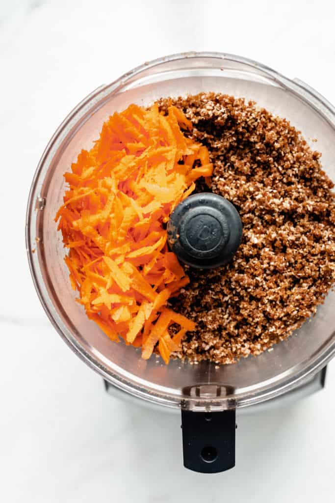 shredded carrots and raw carrot cake dough in a food processor