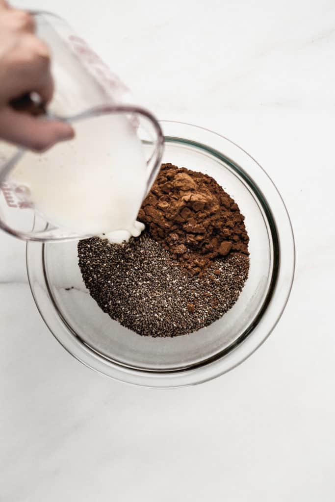A measuring cup pouring almond milk into a bowl of chia seeds