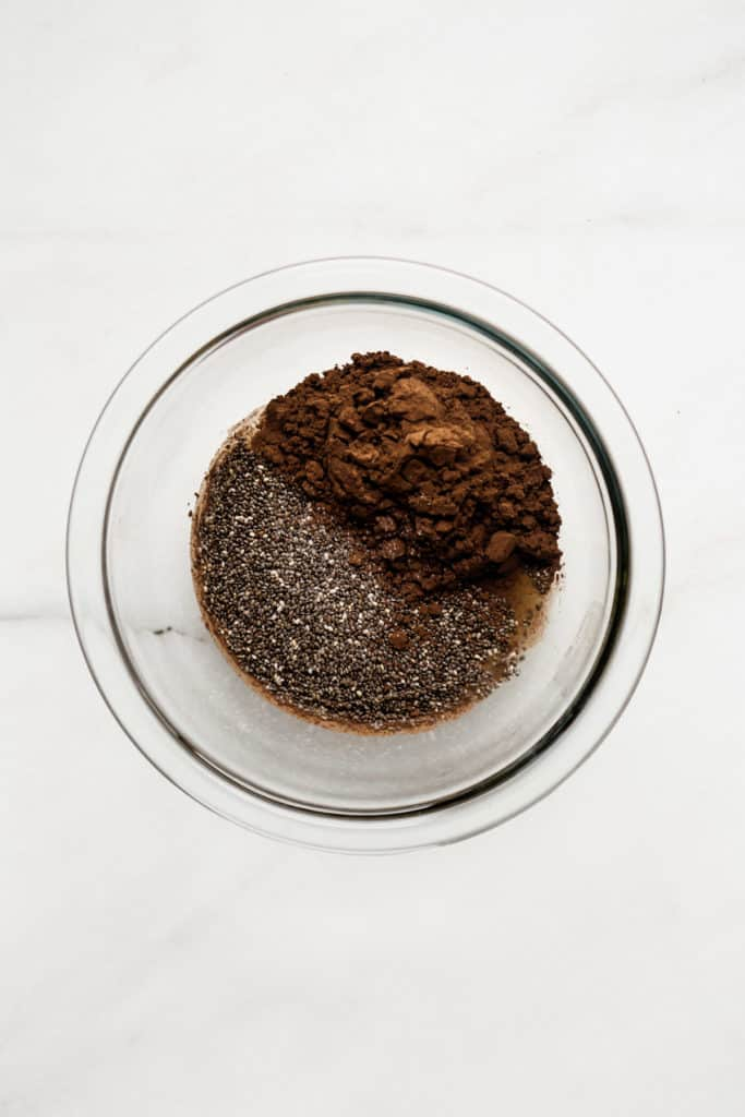 chia seeds and cocoa powder in a clear mixing bowl