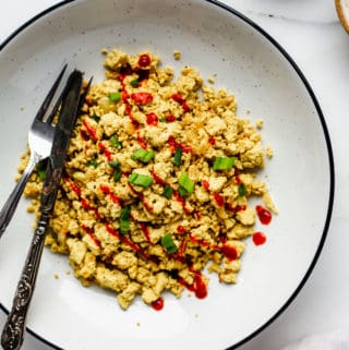 A bowl of scrambled tofu topped with chopped green onions and sriracha