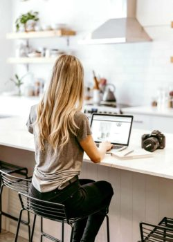 girl sitting at kitchen island on a laptop