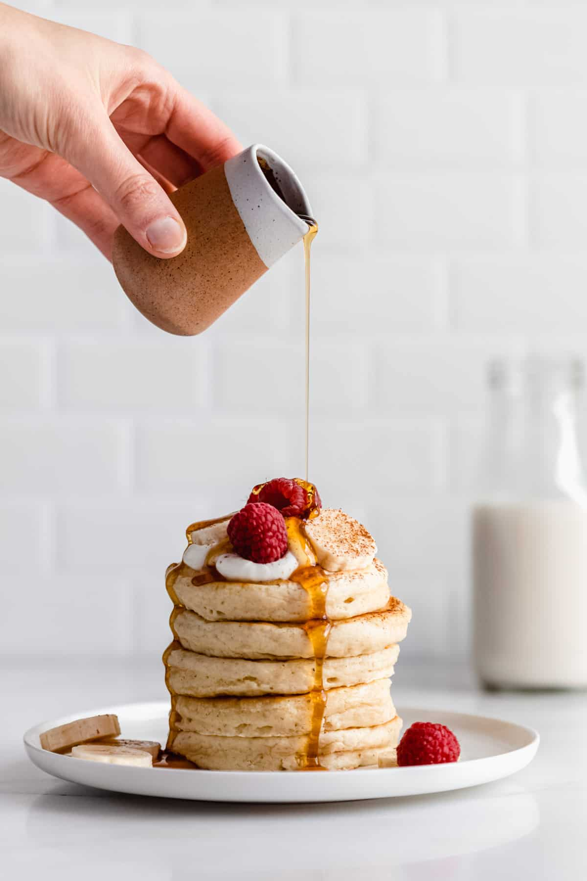 a hand pouring maple syrup onto a stack of vegan oatmeal pancakes