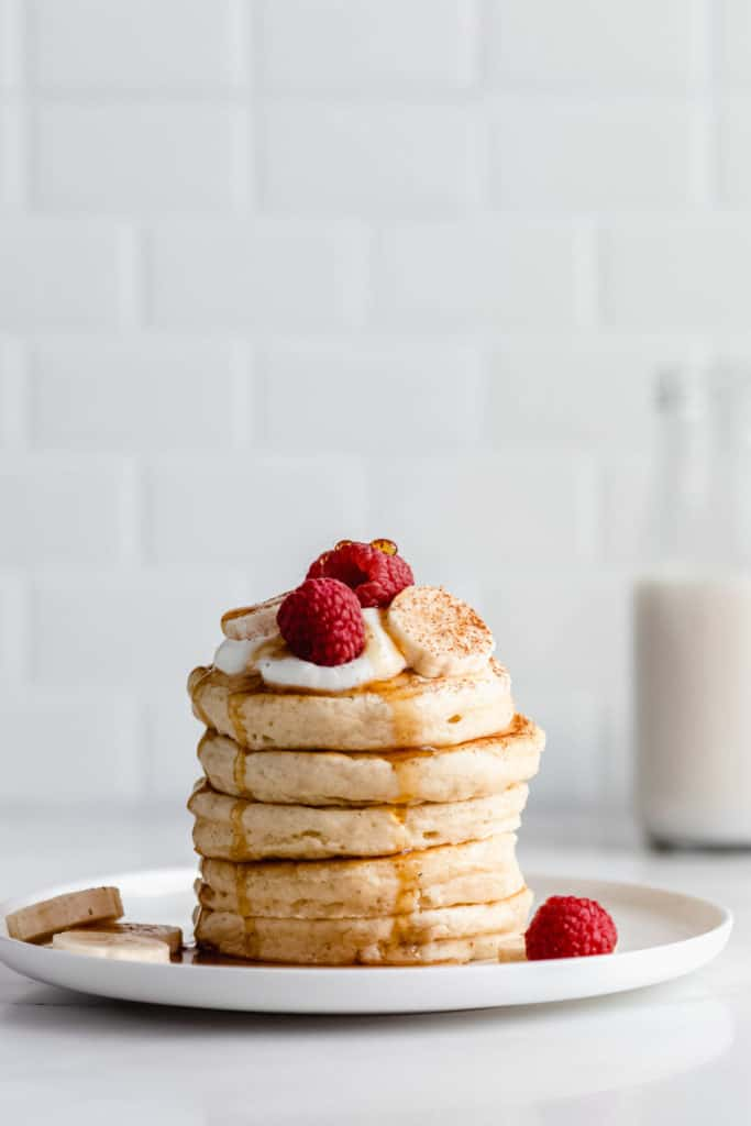 a stack of vegan oatmeal pancakes topped with raspberries and bananas