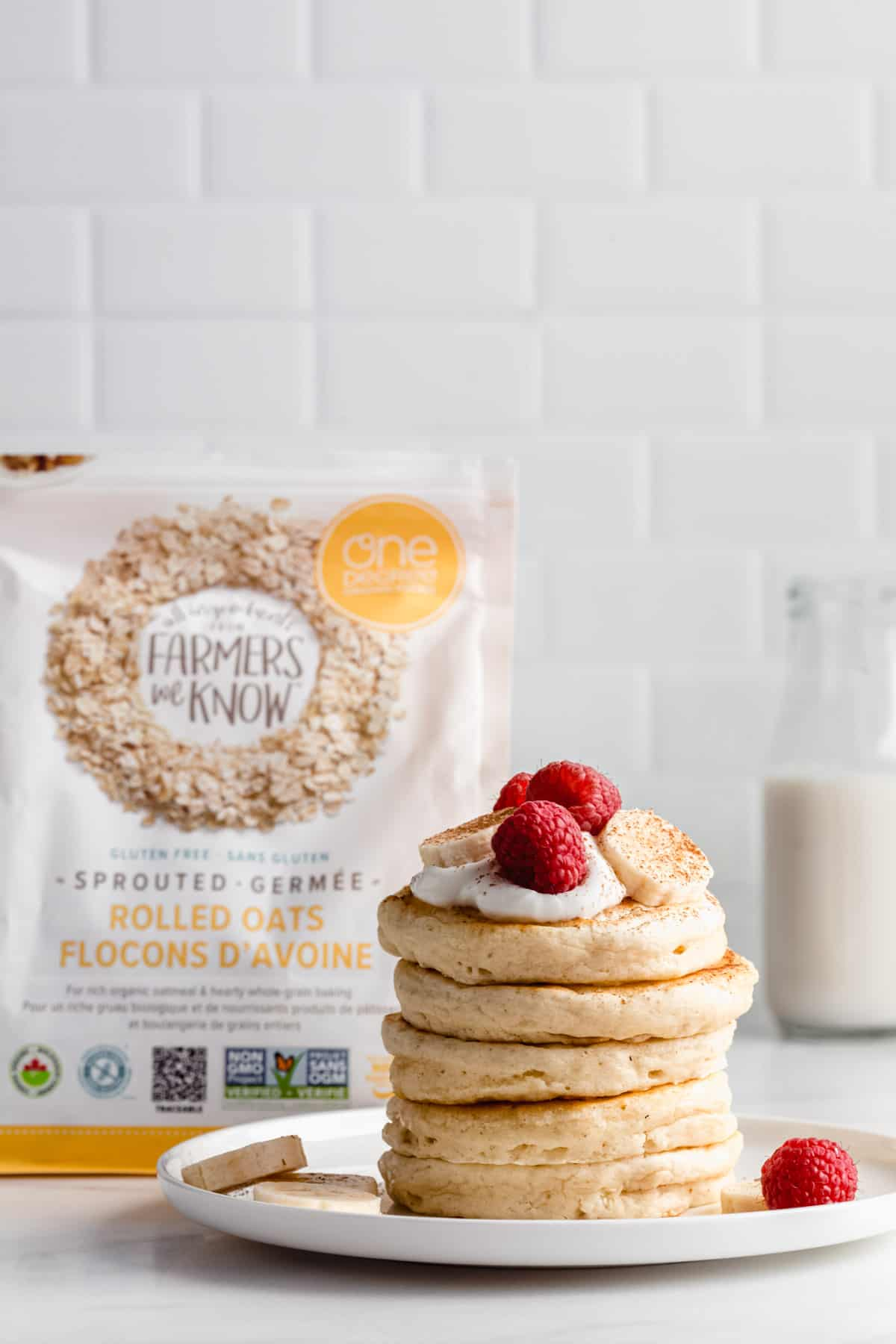 a stack of pancakes with a bag of one degree organic oats in the background