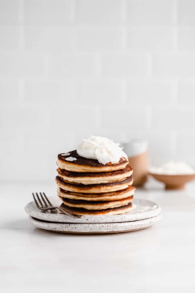 a stack of coconut flour pancakes on a white speckled plate with a fork on the side