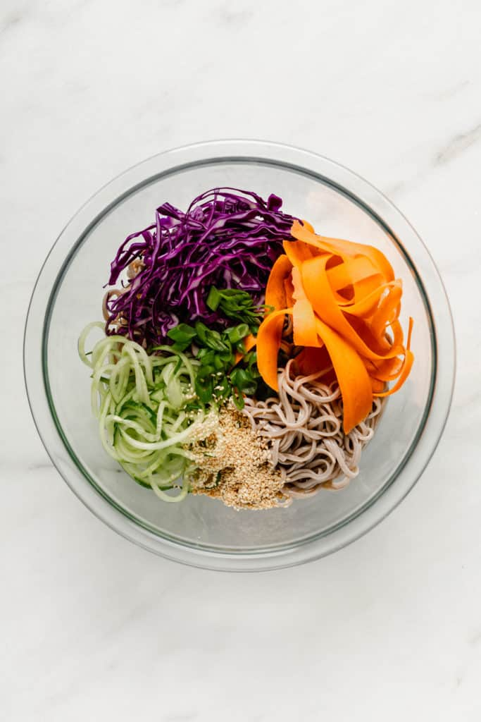 A clear mixing bowl with soba noodles, shredded carrots, cabbage, cucumber, green onions and sesame seeds in it