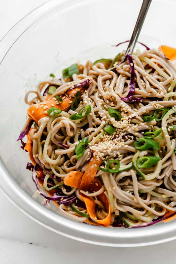 Soba noodle salad with peanut butter sauce in a clear mixing bowl topped with sesame seeds