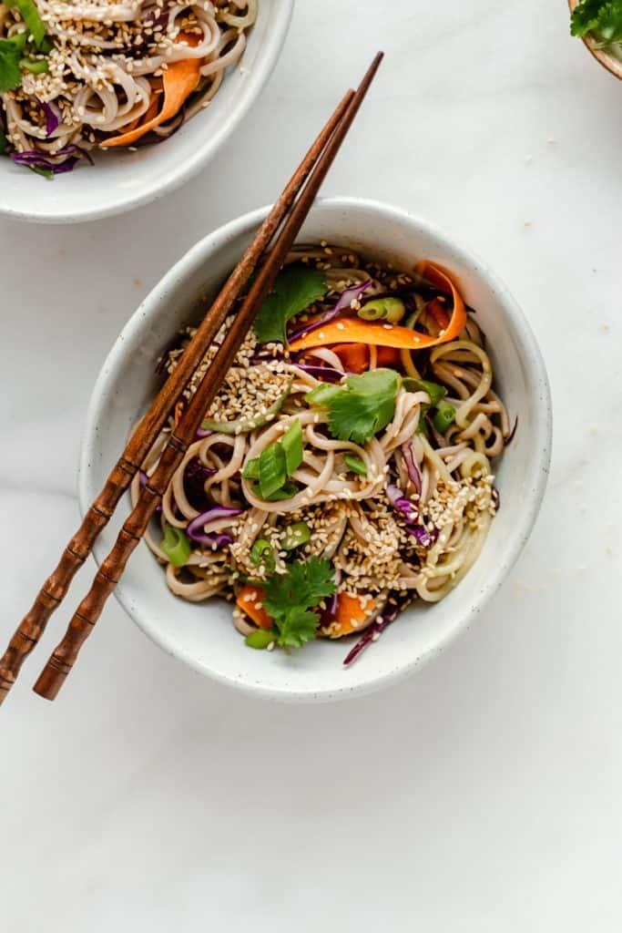 A bowl of soba noodle salad with chopsticks on top