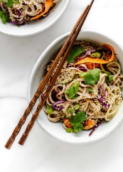 A bowl of soba noodle salad with vegetables topped with cilantro