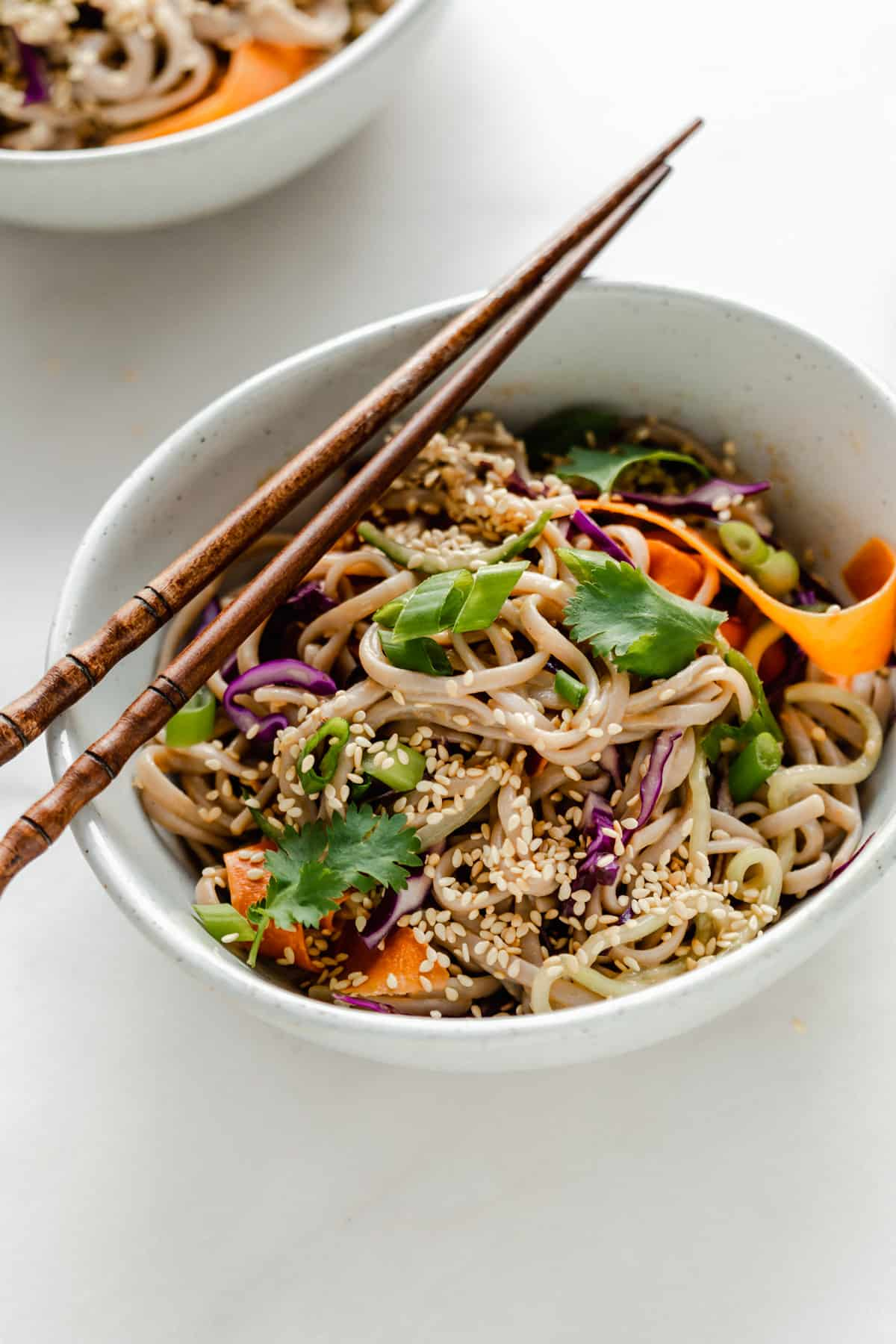 Soba noodle salad with peanut sauce in a white ceramic bowl with wood chopsticks on top