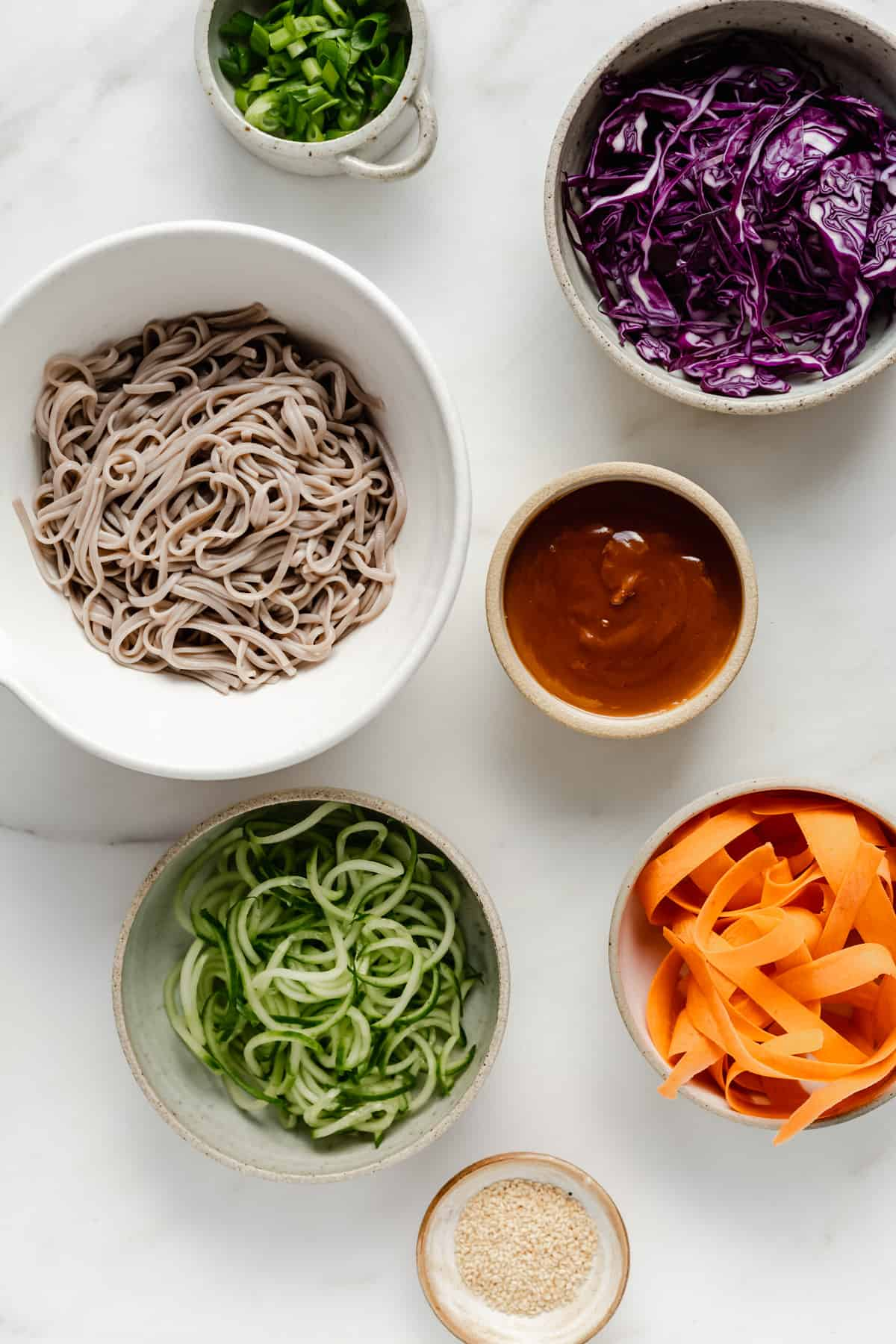 Bowls on a marble counter filled with soba noodles, shredded cabbage, spiralized cucumber, shredded carrots, chopped green onions, sesame seeds and peanut butter sauce