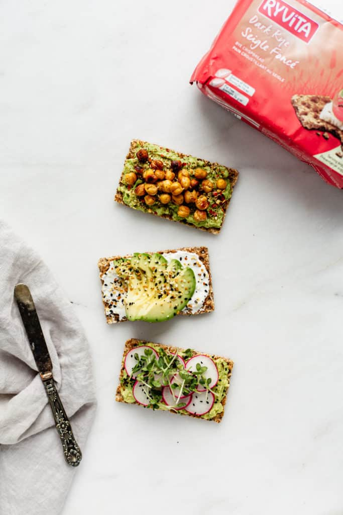 three Ryvita crackers topped with avocado with a package of Ryvita crackers on the side