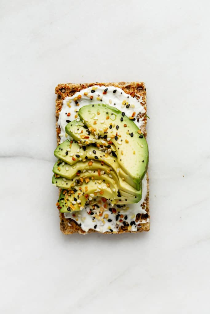 A ryvita cracker topped with cream cheese and avocado