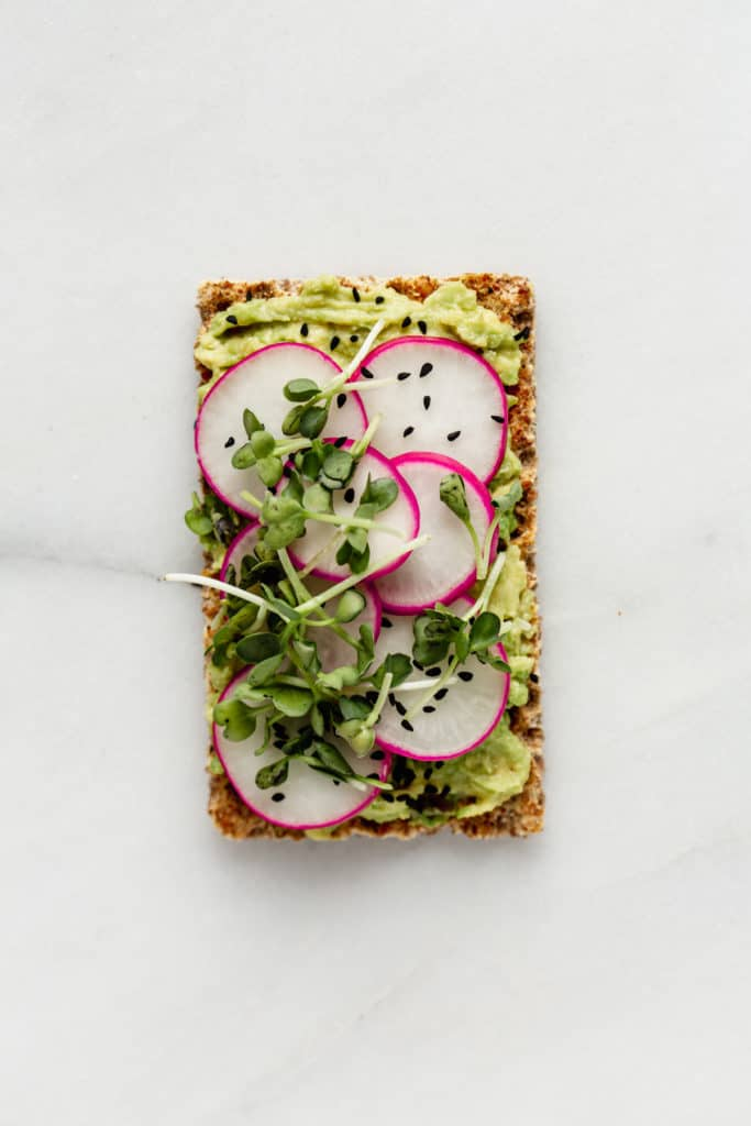 a Ryvita cracker topped with avocado, radishes and radish sprouts