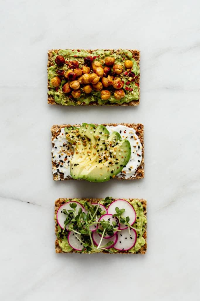 three ryvita crackers topped with avocado