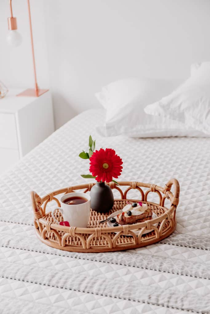 A rattan trey with a flower, tea and french toast on it on a bed