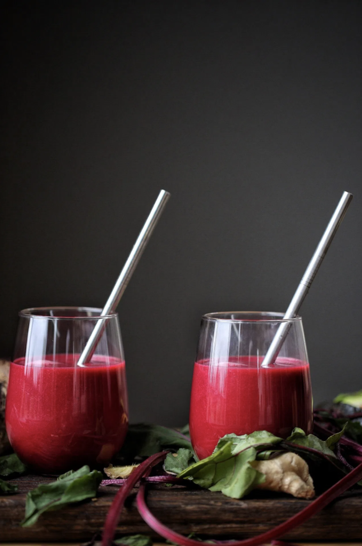 two glasses filled with healthy smoothie recipes made of beets and ginger with stainless steel straw sticking out of both glasses