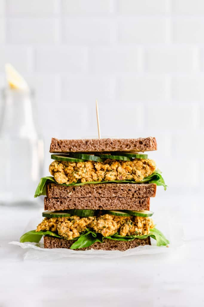 a chickpea salad sandwich cut into half stacked on top of each other