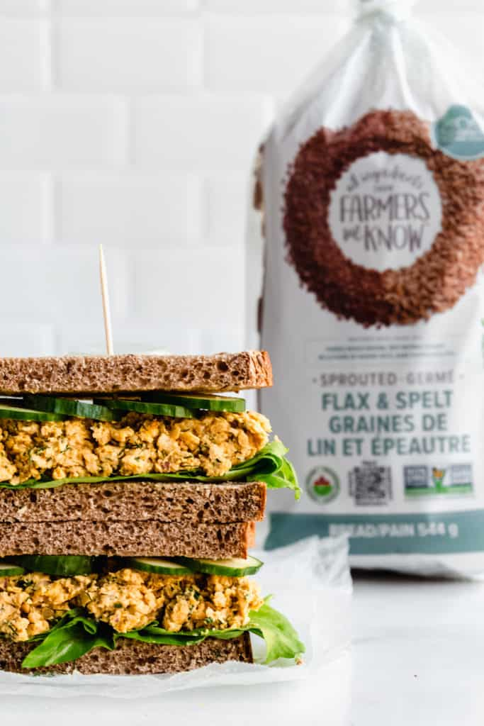 a chickpea salad sandwich with a loaf of bread in the background