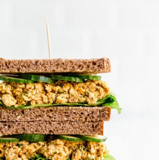 two halves of a chickpea salad sandwich stacked on top of each other