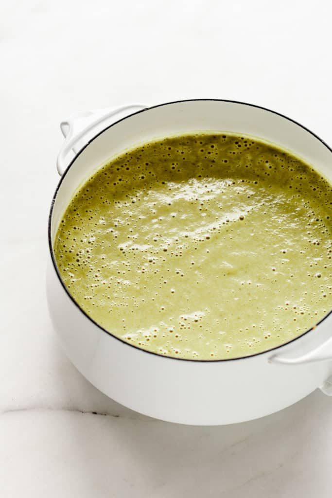 A white pot with creamy vegan asparagus soup in it