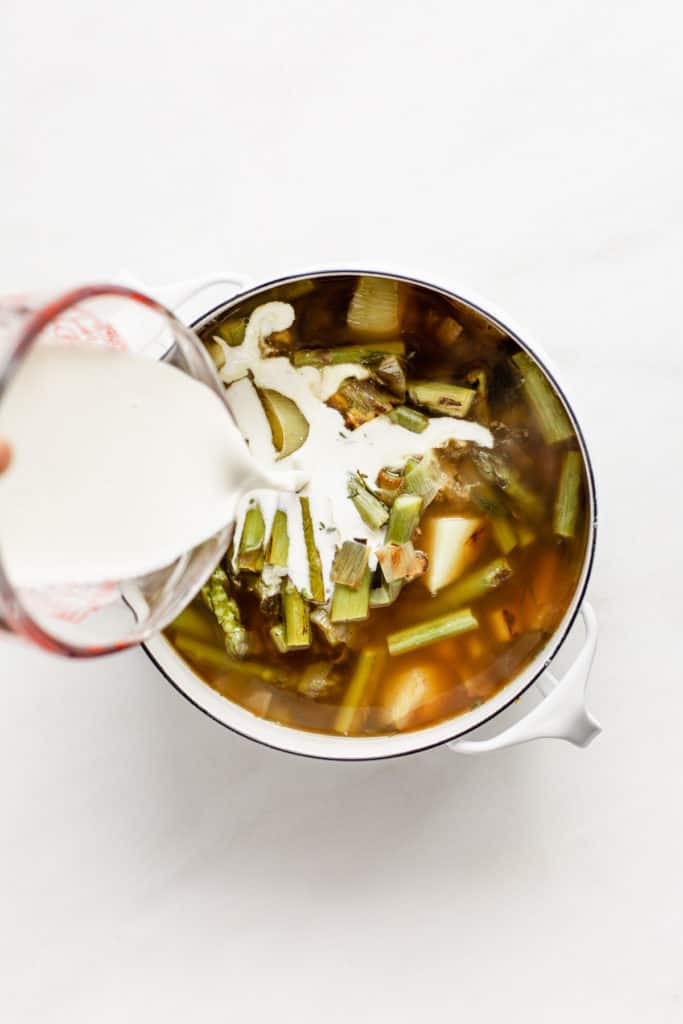 A measuring cup pouring cashew cream into a pot of broth with asparagus and vegetables