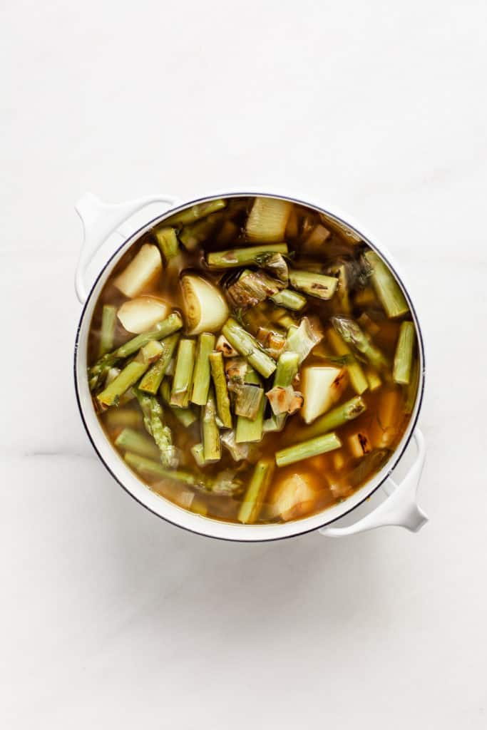 Leaks, asparagus potato and broth in a white pot