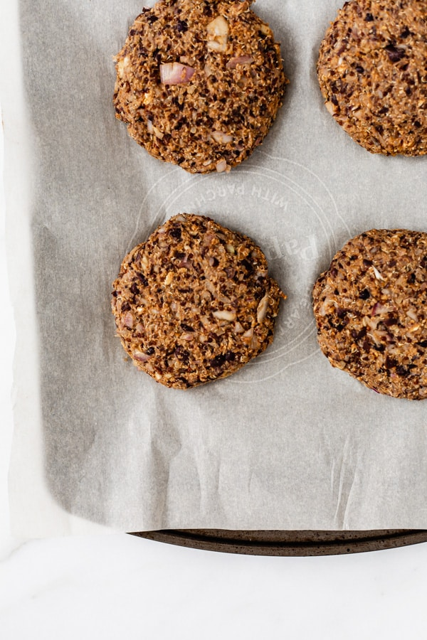 uncooked black bean and quinoa burgers on a baking pan