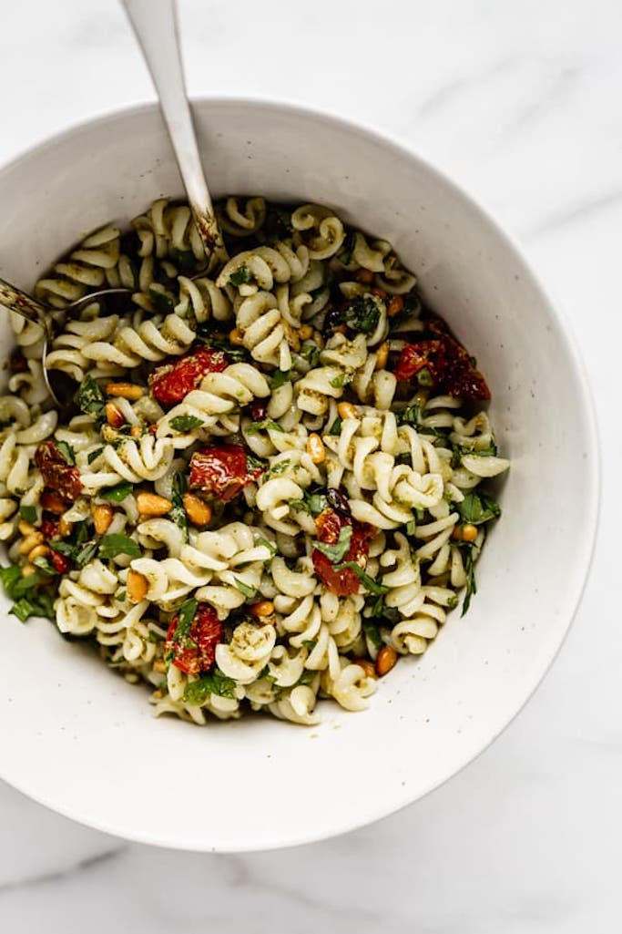 fusilli pasta covered in pesto mixed with sundried tomatoes and pine nuts in a white bowl with a silver spoon