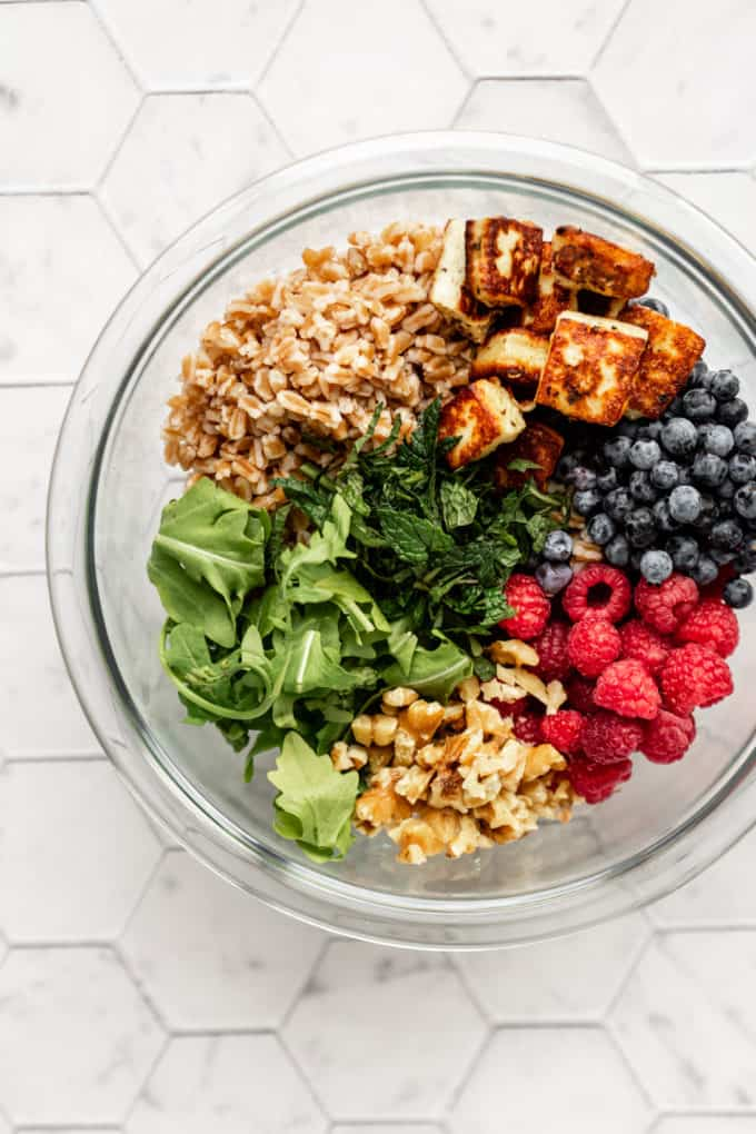 arugula, farro, fried halloumi, blueberries, raspberries and walnuts in a mixing bowl